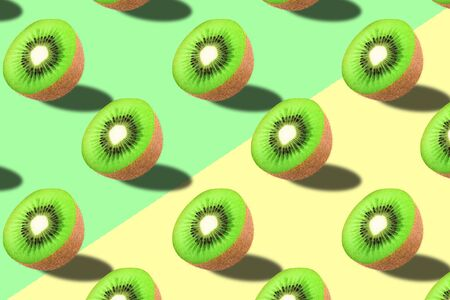 Fruit pattern. Kiwi texture on green pastel and yellow background. From top view. full depth of field. Archivio Fotografico - 129244823