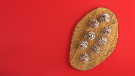 Healthy raw energy balls with cocoa, coconut, sesame, chia on a red background. Vegan chocolate truffles. Copy space. Selective focus. Horizontal and Flat lay. Archivio Fotografico - 129247149