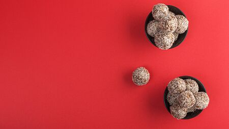 Healthy raw energy balls with cocoa, coconut, sesame, chia on a red background. Vegan chocolate truffles. Copy space. Selective focus. Horizontal and Flat lay. Archivio Fotografico - 129247148