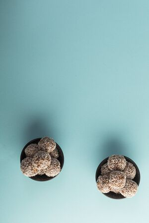 Healthy raw energy balls with cocoa, coconut, sesame, chia on a bright blue background. Vegan chocolate truffles. Copy space. Selective focus. Vertical and Flat lay. Archivio Fotografico - 129247161
