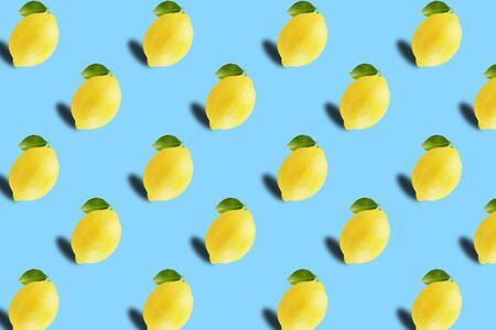 Trendy sunlight Fruit pattern made with whole yellow lemon fruits on bright light blue background. Minimal summer concept. Archivio Fotografico - 129247166
