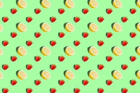 Trendy sunlight Fruit pattern made with yellow lemon slice and strawberry fruits on bright light green background. Minimal summer concept. Archivio Fotografico - 129247894