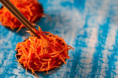 Korean carrot pickled salad on blue background. Fresh carrot on the plates, preserved in vinegar, brine, or a similar solution. Archivio Fotografico - 129247907