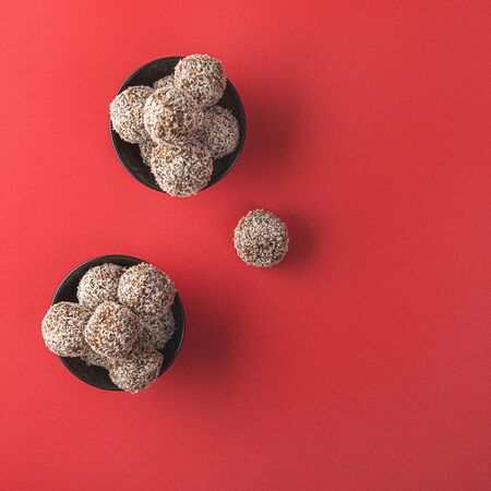 Healthy raw energy balls with cocoa, coconut, sesame, chia on a red background. Vegan chocolate truffles. Copy space. Selective focus. Flat lay. Archivio Fotografico - 129247918