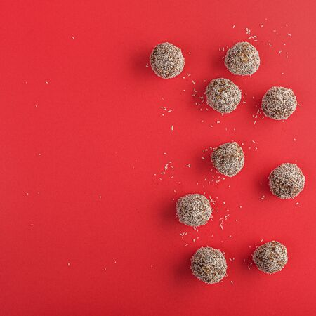 Healthy raw energy balls with cocoa, coconut, sesame, chia on a red background. Vegan chocolate truffles. Copy space. Selective focus. Flat lay. Archivio Fotografico - 129247913