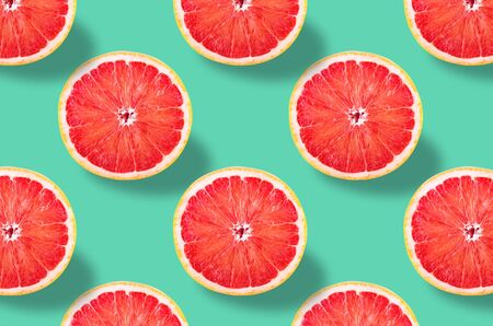 Flat lay fruit pattern of fresh grapefruit slices on green background. Minimal summer fruits pattern for blog or recipe book Archivio Fotografico - 129247929