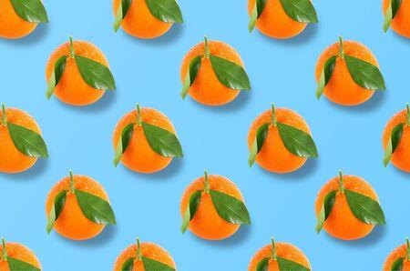 Flat lay fruit pattern of fresh whole orange on blue background. Minimal summer fruits pattern for blog or recipe book Archivio Fotografico - 129247932