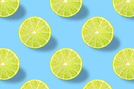 Flat lay fruit pattern of fresh lime slices on blue background. Minimal summer fruits pattern for blog or recipe book Archivio Fotografico - 129248468