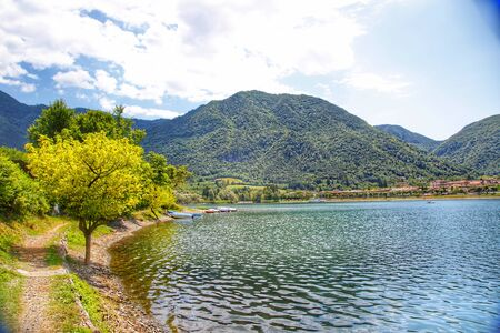 Amazing view landscape on beautiful Lake Idro in Brescia Province, Lombardy, Italy. Scenic small town with traditional houses and clear blue water. Summer vacation for tourists on rich resort in Italy. Archivio Fotografico - 129248474