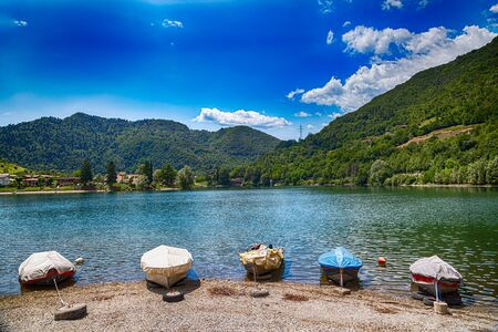 Amazing view landscape on beautiful Lake Idro in Brescia Province, Lombardy, Italy. Scenic small town with traditional houses and clear blue water. Summer vacation for tourists on rich resort in Italy. Archivio Fotografico - 129248479