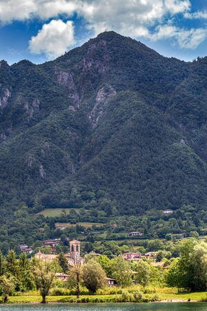 Amazing view landscape on beautiful Lake Idro in Brescia Province, Lombardy, Italy. Scenic small town with traditional houses and clear blue water. Summer vacation for tourists on rich resort in Italy. Archivio Fotografico - 129248477
