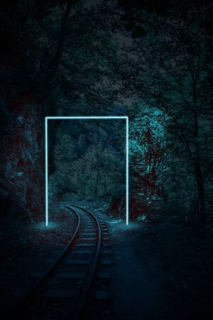 Creative night landscape of rails in the forest layout with neon frame. Supernatural concept. Ultra blue colors.