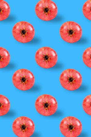 Flat lay pomegranate pattern on blue background. Minimal summer fruits pattern for blog or recipe book on green background. Vertical orientation.