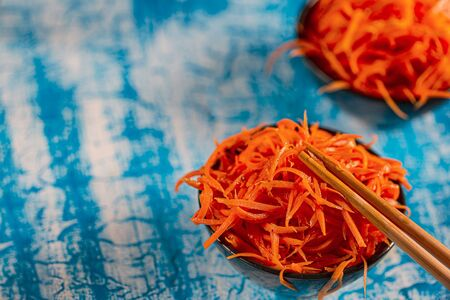 Korean carrot pickled salad on blue background. Fresh carrot on the plates, preserved in vinegar, brine, or a similar solution. Selective focus wit copy space.
