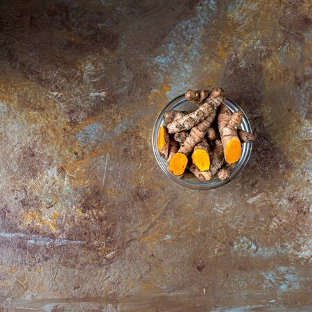Raw organic orange turmeric root, curcuma longa on a brown cooking table. Diet nutrition, health care concept. Indian oriental low cholesterol spices. Copy space