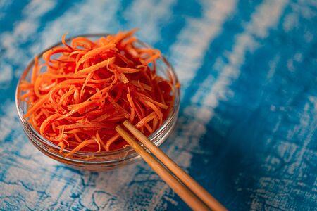 Korean carrot pickled salad on blue background. Fresh carrot on the plates, preserved in vinegar, brine, or a similar solution.