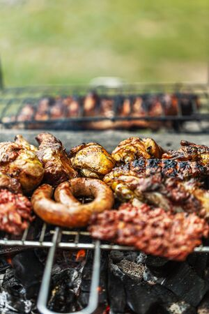 Barbecue fried sausages background, close-up. Sausage kebab on coals. Traditional cooking. Family picnic in the open air. Selective focus.