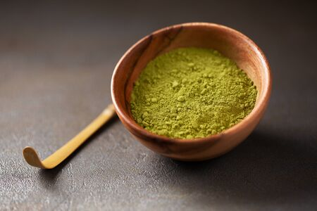 Matcha green tea powder in a wood bowl on concrete surface. It is a rich source of antioxidants and polyphenols. Selective focus with copy space in minimal style.