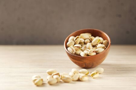 Pistachios in a wood bowl on concrete surface. Edible pale green seed of an Asian tree. Selective focus in minimal style. Stock Photo