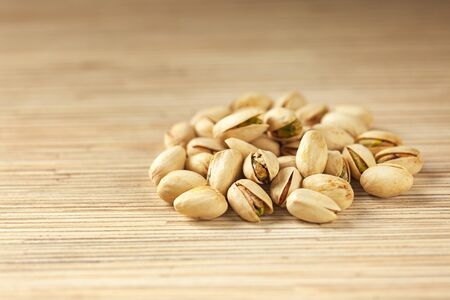 Heap of pistachios on wood surface. Edible pale green seed of an Asian tree. Selective focus in minimal style.