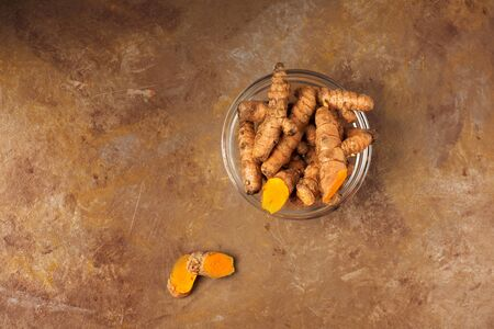 Raw organic orange turmeric root, curcuma longa on a brown cooking table. Diet nutrition, health care concept. Indian oriental low cholesterol spices. Copy space, horizontal..