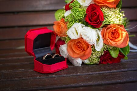 close up on a romantic wedding coral, red and white flower bouquet and rings resting on on a bench. bridal concept. selective focus, nobody Stock Photo