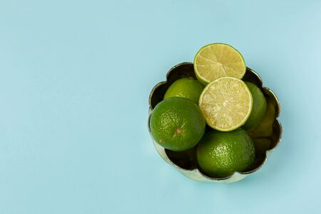 Fresh Limes in fruit bowl over a light blue background with large copy space. Minimal concept in flat lay.