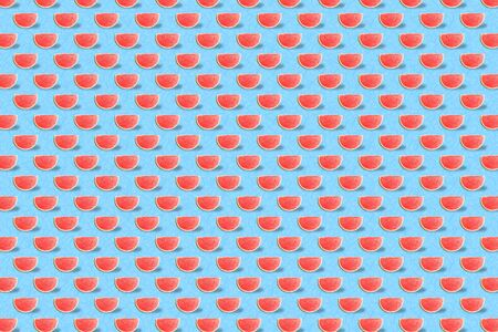 Fruit pattern made with red watermelon slice on blue background. Minimal summer fruits pattern for blog or recipe book.