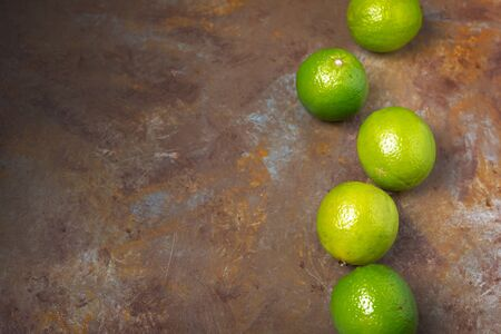 Fresh Limes on rust background with large copy space. Minimal concept in flat lay.