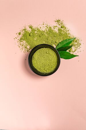 Matcha green tea powder in a black ceramic bowl on coral surface. It is a rich source of antioxidants and polyphenols. Selective focus with copy space in minimal style. Vertical orientation.