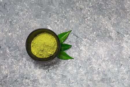 Matcha green tea powder in a black ceramic bowl on concrete surface. It is a rich source of antioxidants and polyphenols. Selective focus with copy space in minimal style. Horizontal orientation.