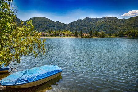 Tourist attraction on Lake Idro in Brescia Province, Lombardy, Italy. Scenic small town with traditional houses and clear blue water. Summer vacation for tourists on rich resort in Italy.