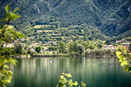 Amazing view landscape on beatiful Lake Idro in Brescia, Lombardy, Italy. Scenic small town with traditional houses and clear blue water. Summer vacation for tourists on rich resort in Italy.