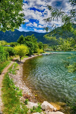 Beatiful landscape on Lake Idro in Brescia Province, Lombardy, Italy. Scenic small town with traditional houses and clear blue water. Summer vacation for tourists on rich resort in Italy. 스톡 콘텐츠