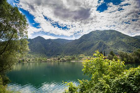 Landscape on beatiful Lake Idro in Brescia Province, Lombardy, Italy. Scenic small town with traditional houses and clear blue water. Summer vacation for tourists on rich resort in Italy.