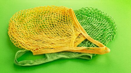 Two reusable cotton net bags or mesh bags on coloured background