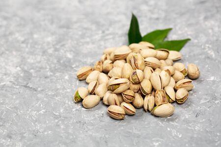 Heaps of pistachio nuts over concrete surface