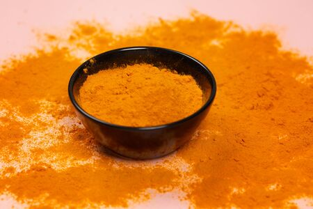 Curcuma longa powder in a black ceramic bowl on concrete surface. indian spice, healthy seasoning ingredient for vegan cuisine concept. Selective focus with copy space in minimal style. Horizontal. Stock Photo