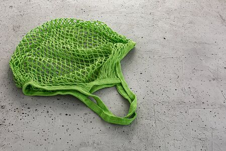 Green eco cotton string bag on a concrete background