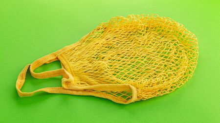 One reusable cotton net bags or mesh bags on coloured background