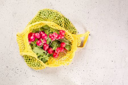 Fresh harvest vegetables, in shopping eco-friendly mesh bag, on concrete background. Concept Organic vegetable harvest. Top view Flat lay. Archivio Fotografico - 132228906
