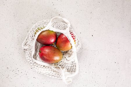 Fresh harvest vegetables, in shopping eco-friendly mesh bag, on concrete background. Sustainability our planet from pollution by giving up the use of non-biodegradable material. Top view Flat lay Archivio Fotografico - 132229064