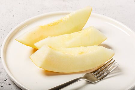 Ripe Sliced melon fruit, in white dish, rich in mineral salts and vitamins. Home kitchen colse up. Selective focus. Archivio Fotografico - 132603958
