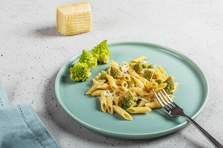 Pasta with Roman broccoli is a delicate first vegetarian that whets the appetite, very quick to prepare, copy space. Archivio Fotografico - 132811378