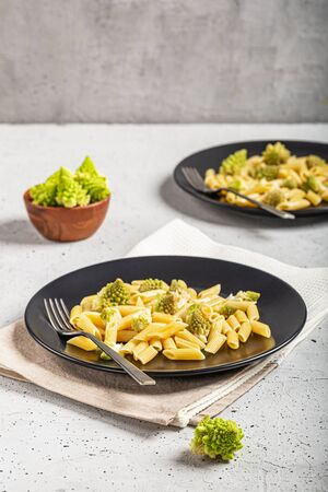 Pasta with Roman broccoli is a delicate first vegetarian that whets the appetite, very quick to prepare, copy space. Archivio Fotografico - 132814115