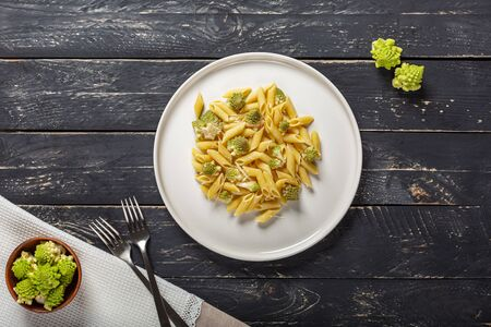 Pasta with Roman broccoli is a delicate first vegetarian that whets the appetite, very quick to prepare, Top view, copy space. Archivio Fotografico - 132813018