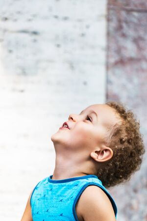 Cute baby boy 3 year old who looks up happy and satisfied over against the background of the gray wall. Childhood concept.