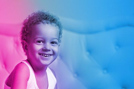 Cute baby boy 3 year old who smiles satisfied in the morning against the background of the bed in the blue and magenta neon theme. Indoor. Childhood concept.