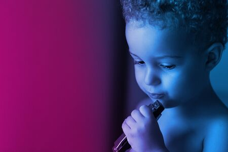 Cute baby boy 3 year old playing the harmonica, on the neon blue and magenta background.. Outdoor. Childhood concept.