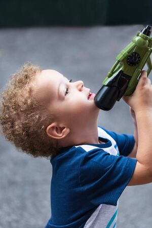 Cute baby boy 3 year old playing with toy gun in the park. Outdoor. Childhood concept. Zdjęcie Seryjne